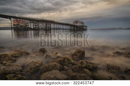 Low Tide At Dusk At Mumbles Pier In Swansea, South Wales Uk, Showing Mumbles Pier And Lifeboat Stati