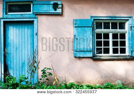 Grungy Facade Of An Empty Abandoned House With Blue Painted Wooden Door And Shutter