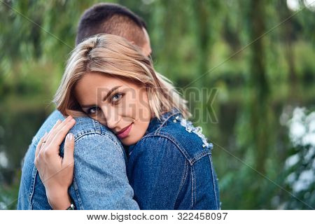 Young Beautiful Woman Hugging Her Boyfriend With Love Outdoors. Caucasian Couple In Park. Tenderness