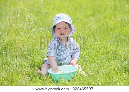 A Happy Happy Happy Boy Frolicking In The Basin. Outdoors In Summer, Spraying Water. .child Plays Wi