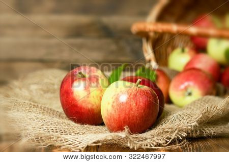 Red Organic Apples In A Wicker Basket On A Wooden Background.