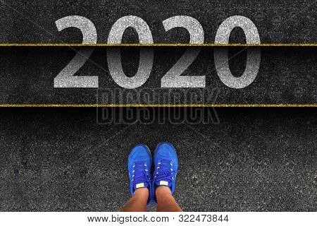 Happy New Year 2020. Man Legs In Sneakers Standing Next To Stairs With Number 2020