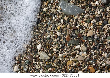 Thin White Foam And The Many Small Bubbles On The Glittering Sea Water With The Colorful Pebbles Und
