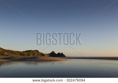Clear Blue Sky At Three Cliffs Bay, A Well Known Coastal Beauty Spot On The Gower Peninsula In Swans