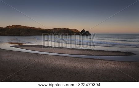 The Ever Changing Beach At Three Cliffs Bay, A Well Known Coastal Beauty Spot On The Gower Peninsula