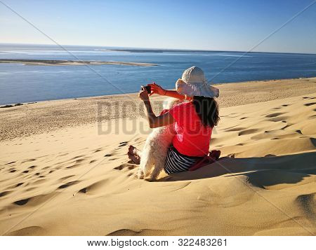 Young Woman Sitting On A Dune With Her Pet, Photographing With Smart Phone Beautiful Landscape. Beau