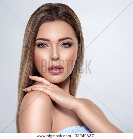 Beauty face of the young beautiful woman  with a fresh healthy skin. Closeup portrait of an attractive caucasian female. Skin care concept. Woman with a smokey eye makeup. Beauty treatment.