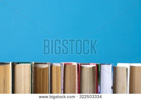 Simple Composition Of Hardback Books, Raw Books On Wooden Deck Table And Blue Background. Stacking B