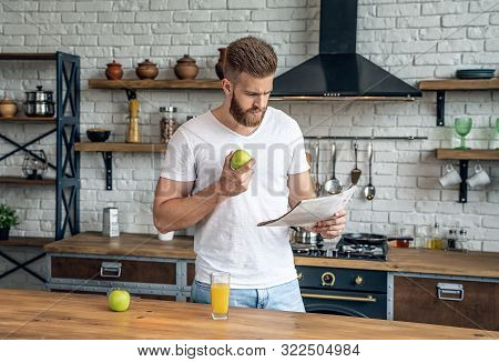 Handsome Bearded Man Eating An Apple And Reading A Fresh Newspaper. Stands In The Kitchen In A White