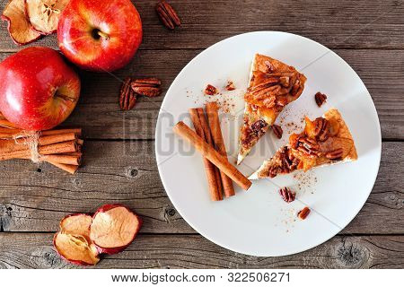 Two Slices Of Caramel Apple Pecan Cheesecake. Top View Table Scene With A Rustic Wood Background. Au
