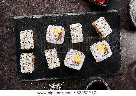 Rainbow uramaki sushi rolls with rice, bacon, processed cheese, tomato, green onion, sesame and nori on black slate plate background closeup. Macro shot of fusion maki sushi in Japanese restaurant poster