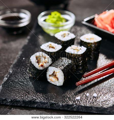 Macro shot of eel hosomaki sushi on natural black slate plate background with selective focus. Thin small unagi maki sushi rolls with rice, eel and nori closeup