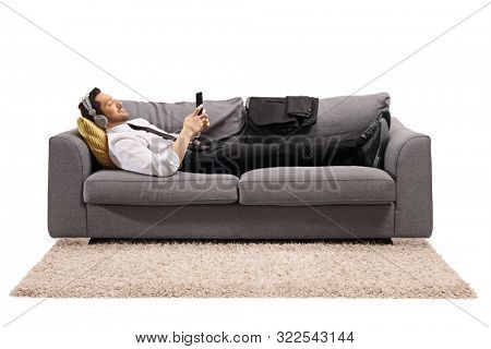 Full length shot of a businessman lying on a sofa and listening to music isolated on white background