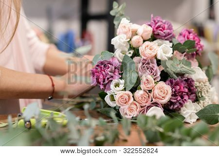 Close-up Flowers In Hand. Florist Workplace. Woman Arranging A Bouquet With Roses, Carnation And Oth