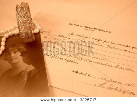 Old photo of young woman with document and jewellery