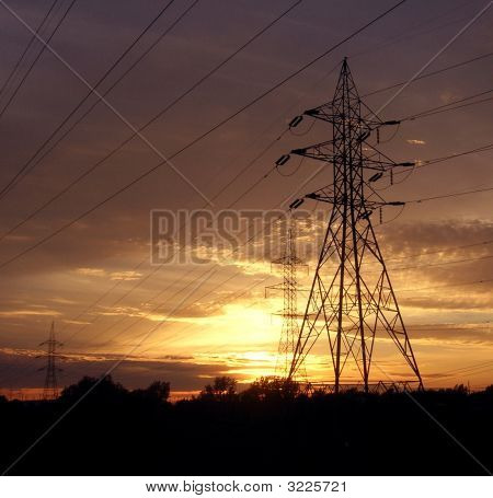 Power tower silhouette against the setting sun