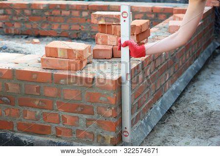 Bricklayer Using A Spirit Level To Check Bricklaying Wall Outdoors. Bricklaying Basics Masonry Techn