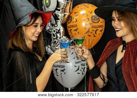 Group of young adult and teenager people celebrating a Halloween party carnival Festival in Halloween costumes drinking alcohol cocktail poster