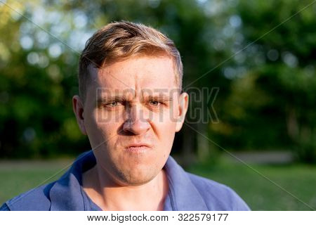 Enraged Infuriated Man. Portrait Of A Young Man On Nature Background. Emotion Facial Expression.