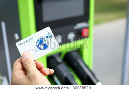 Focus On Male Hand With Bankcard. Different Ways Of Payments On Electric Car Charging Station. Elect