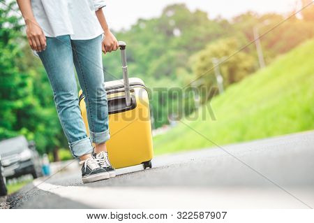 Closeup Lower Body Of Woman Handling Yellow Trolly Luggage Along Road Trip With Mountain Hill Backgr