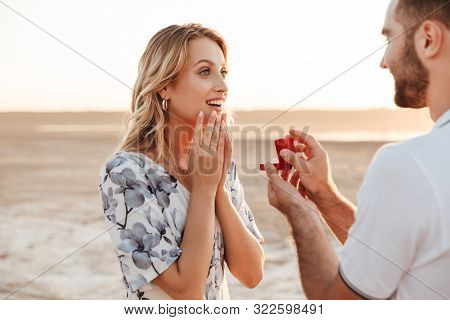Photo of romantic man making proposal to his amazed woman with ring in gift box while walking on sunny beach