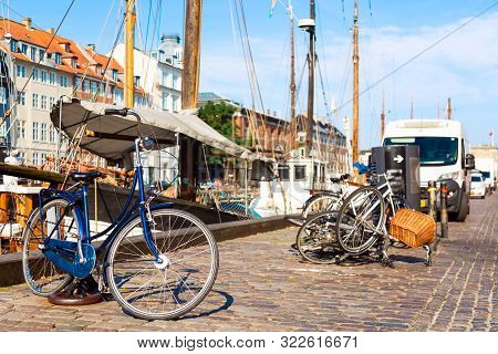 poster of Copenhagen iconic view. Famous old Nyhavn port in the center of Copenhagen, Denmark during summer sunny day with a bicycle