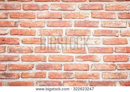 Orange brick wall concrete or stone texture background, wallpaper limestone abstract to flooring and homework/Brickwork. Stonework clean grid uneven interior rock old. Old repaired weathered brick wall for background or wallpaper. Copy space. poster