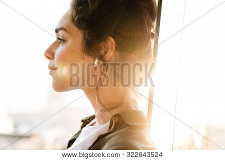 Image of lovely brunette woman listening to music with earpods while standing at terrace outdoors in morning
