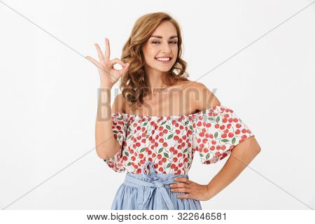 Photo of a happy smiling pleased woman posing isolated over white wall background make okay gesture.