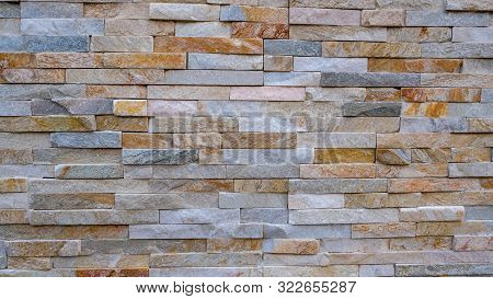 Wild Yellow Decorative Stone Background. Artificial Yellow Decorative Bricks Wall. Construction Made