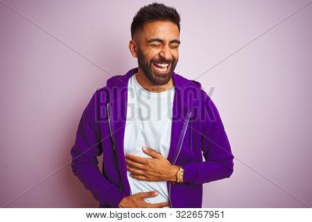 Young indian man wearing purple sweatshirt standing over isolated pink background smiling and laughing hard out loud because funny crazy joke with hands on body.