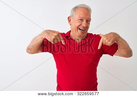 Senior grey-haired man wearing red polo standing over isolated white background looking confident with smile on face, pointing oneself with fingers proud and happy.
