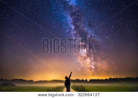 Landscape With Milky Way Galaxy And Man Silhuette Pointing To The Stars