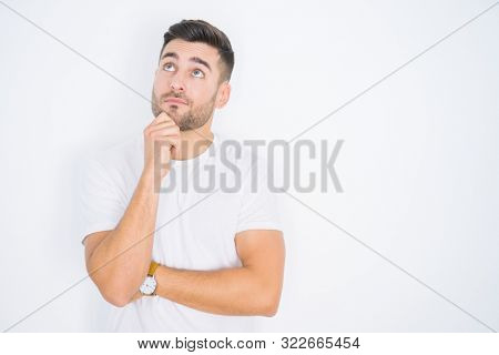 Young handsome man wearing casual white t-shirt over white isolated background with hand on chin thinking about question, pensive expression. Smiling with thoughtful face. Doubt concept.