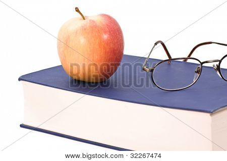 Glasses and apple on a big blue book