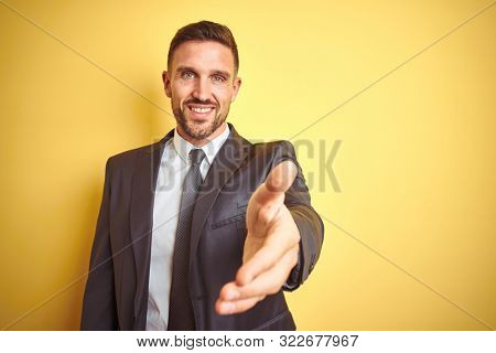 Young handsome business man over yellow isolated background smiling friendly offering handshake as greeting and welcoming. Successful business.