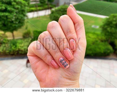 Light Nude Manicure With Blah Blah Blah Word On One Finger. Blah Word.