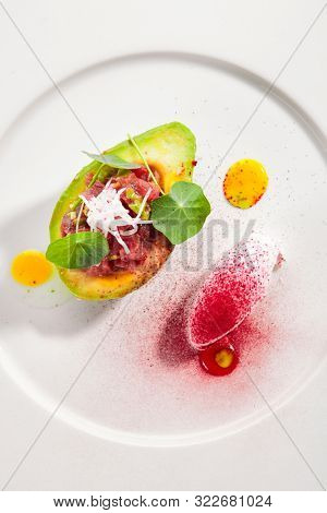Tuna tartar made from raw fish served in avocado with lime ice cream on white restaurant plate isolated. Exquisite serving yellowfin sashimi tatar in alligator pear with gourmet dessert topview poster