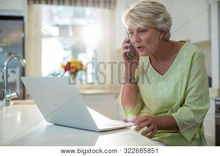 Senior woman talking on mobile phone while using laptop at home