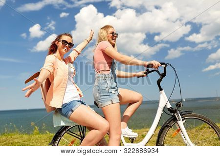 leisure and friendship concept - happy smiling teenage girls or friends riding bicycle together at seaside in summer