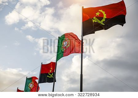 Row Of Portugal And Angola Flags Waving In The Wind Against White Cloudy Blue Sky Together.