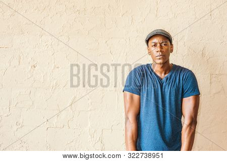 Portrait Of Young African American Man In New York. A Black Guy Wearing Blue V Neck T Shirt, Flat Ca
