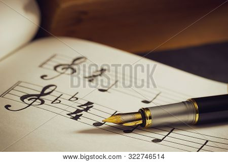 Music Notes And Old Book On Wooden Table Background In Morning Light. Writing Chords By Vintage Pen.