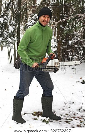 A Man In Boots And A Chainsaw In The Woods With A Fierce Facial Expression, Winter
