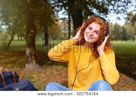Smiling Happy Red Hair Student Girl In Headphones Outside In Autumn Park