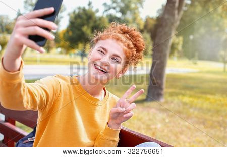 Smiling Happy Red Hair Student Girl Taking Picture Of Herself On The Phone Outside In Autumn Park