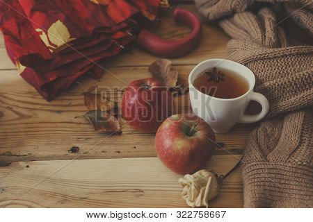 Cold Autumn Days. A Cup Of Tea With Fall Leafs And Dried Rose Flowers On Wooden Table. Warming Herba
