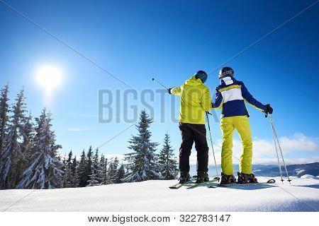 Male Skier Showing With Ski Poles On Sun High In Blue Sky Over Winter Mountains. Back View Of Couple