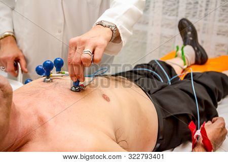 Cardiologist Is Attaching Vacuum Sensors To Elder Patient For Recording Ecg Or Ekg Cardiogram Test.